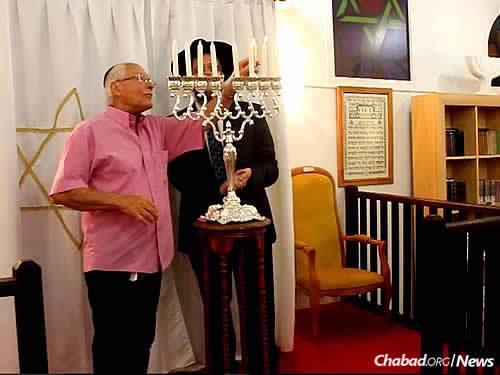 Guy Flak lights the Chanukah menorah.