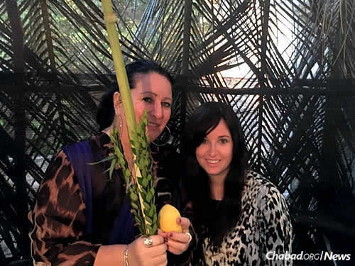 Bassie Sabbach shakes the lulav with Hannah Mireille-Winifred.